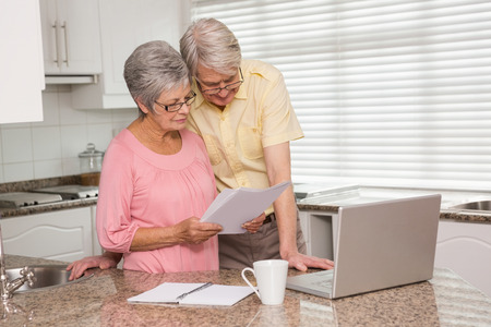Senior couple paying their bills with laptop at home in the kitchen