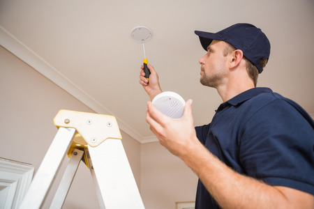 Handyman installing smoke detector with screwdriver on the ceiling