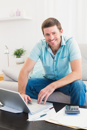 Smiling man on a laptop sitting on a sofa at home paying his bills