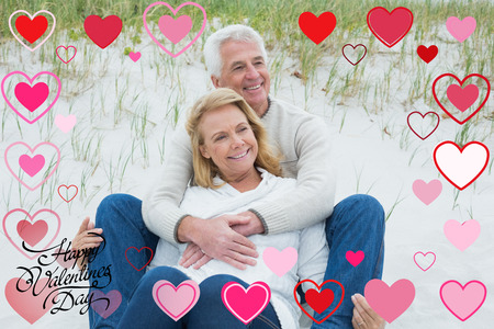 Romantic senior couple relaxing at beach against happy valentines day