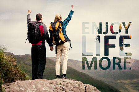 Photo for Excited couple reaching the top of their hike and cheering against enjoy life more - Royalty Free Image