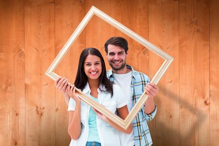 Photo pour Happy young couple holding picture frame against wooden planks - image libre de droit
