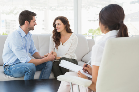 Photo pour Reconciled couple smiling at each other in the therapist office - image libre de droit