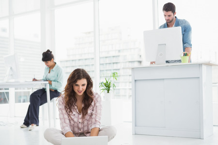 Cheerful businesswoman sitting on the floor using laptop with colleagues behind her
