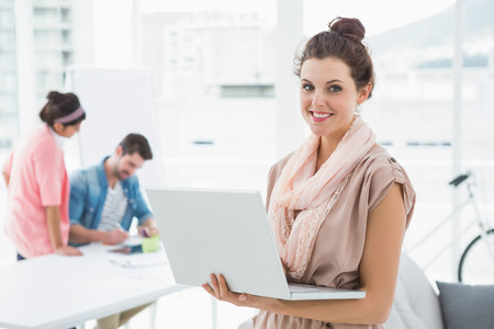 Happy businesswoman standing and using laptop with colleagues behind her