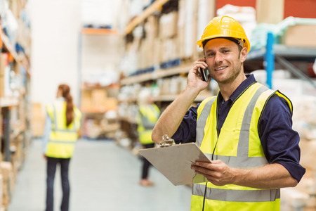 Photo for Warehouse worker talking on the phone holding clipboard in a large warehouse - Royalty Free Image