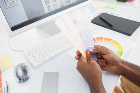 Designer holding colour sample and choosing in the office