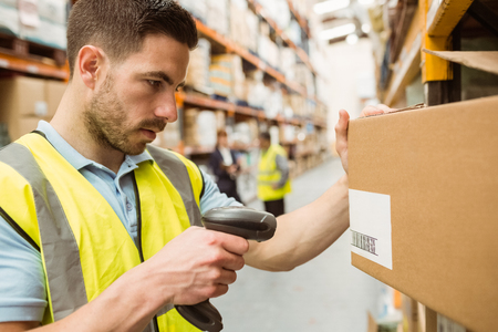 Warehouse worker scanning barcodes on boxes in a large warehouse