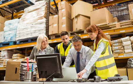 Photo for Warehouse managers and worker working on laptop in a large warehouse - Royalty Free Image