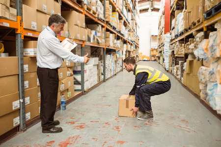 Photo pour Manager watching worker carrying boxes in a large warehouse - image libre de droit