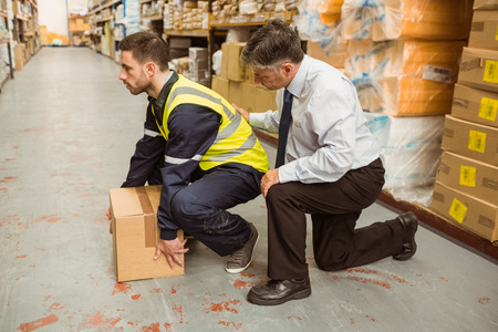 Photo for Manager training worker for health and safety measure in a large warehouse - Royalty Free Image