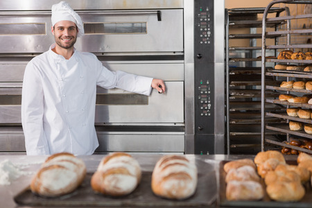 Photo pour Happy baker leaning on professional oven at the bakery - image libre de droit