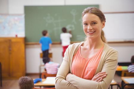 Foto de Pretty teacher smiling at camera at back of classroom at the elementary school - Imagen libre de derechos