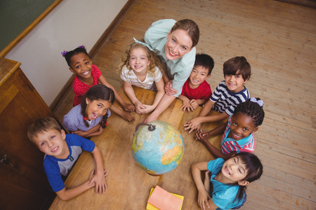 Photo pour Cute pupils smiling around a globe in classroom with teacher at the elementary school - image libre de droit