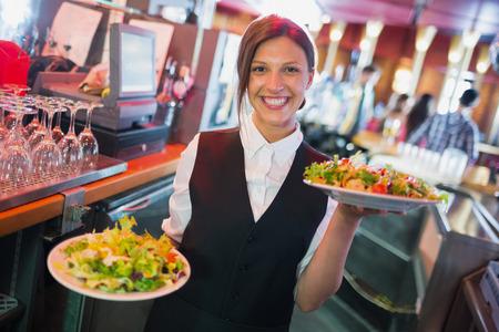 Photo pour Pretty barmaid holding plates of salads in a bar - image libre de droit