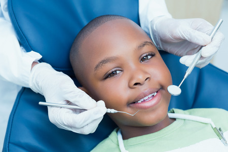 Photo pour Close up of boy having his teeth examined by a dentist - image libre de droit