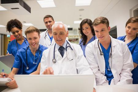 Photo pour Medical students and professor using laptop at the university - image libre de droit