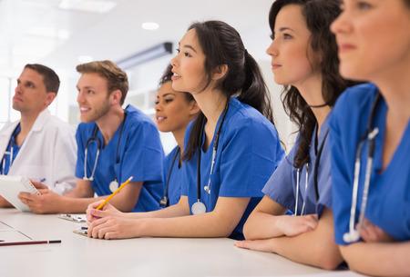 Photo pour Medical students listening sitting at desk at the university - image libre de droit