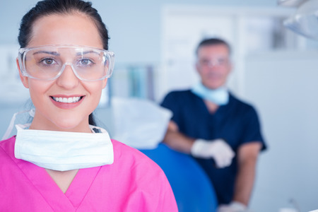 Smiling assistant with protective glasses at the dental clinic