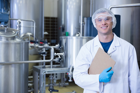 Smiling scientist looking at camera holding a clipboard in the factory
