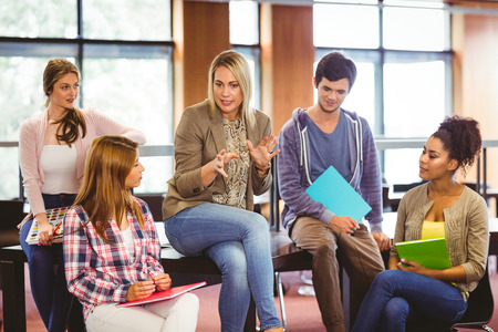 Happy students talking with their teacher in the library