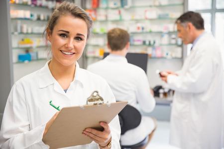 Junior pharmacist writing on clipboard at the hospital pharmacy