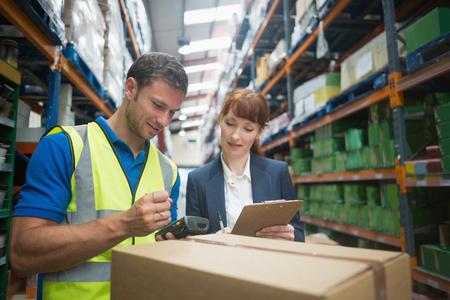 Foto de Portrait of manual worker and manager scanning package in the warehouse - Imagen libre de derechos