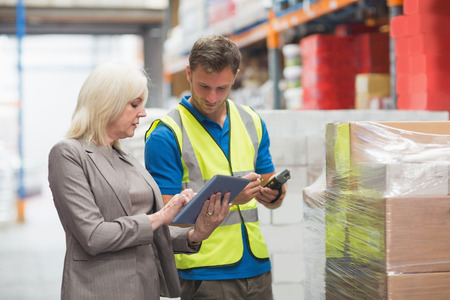 Photo for Manager using tablet while worker scanning package in warehouse - Royalty Free Image