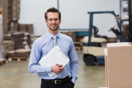 Photo pour Portrait of manager holding clipboard in warehouse - image libre de droit