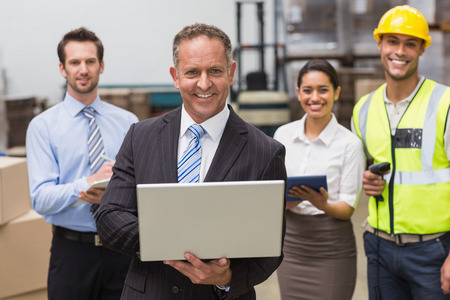 Smiling boss using laptop in front of his employees in a large warehouse