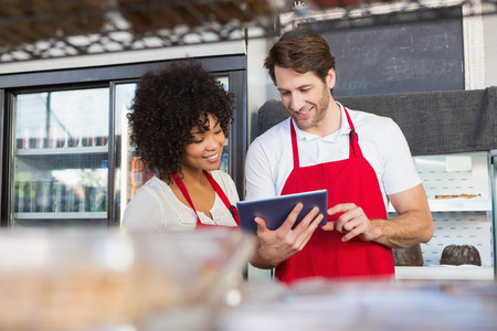 Photo for Colleagues in red apron using tablet at the bakery - Royalty Free Image