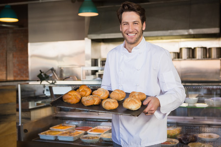 Portrait of smiling baker holding tray with bread at the bakery
