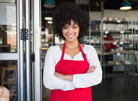 Photo for Pretty server in red apron with arms crossed at the bakery - Royalty Free Image