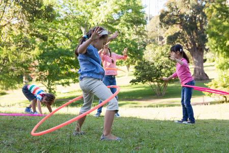 Foto de Little friends playing with hula hoops in park on a sunny day - Imagen libre de derechos