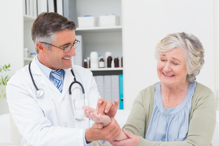 Happy male doctor examining patients hand at table in clinic