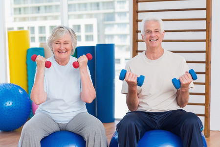 Portrait of happy senior couple lifting dumbbells while sitting on exercise ball at gymの写真素材