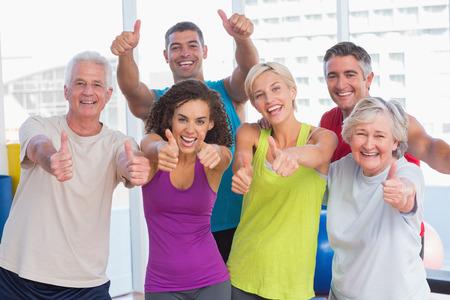 Foto de Portrait of happy friends gesturing thumbs up in fitness club - Imagen libre de derechos