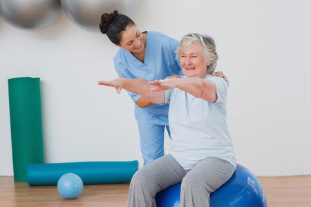 Happy instructor assisting senior woman in exercising at gym