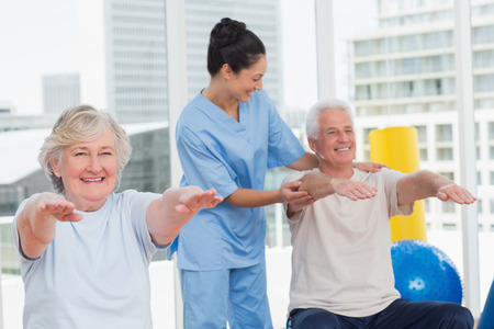 Happy young trainer assisting senior couple in exercising at gym