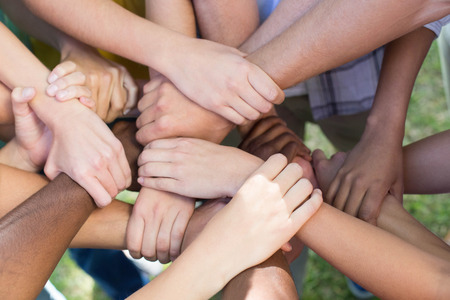 Photo pour Friends putting their hands together on a sunny day - image libre de droit