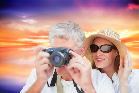 Vacationing couple taking photo against purple sky with orange clouds
