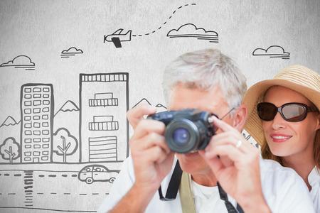 Vacationing couple taking photo against white background