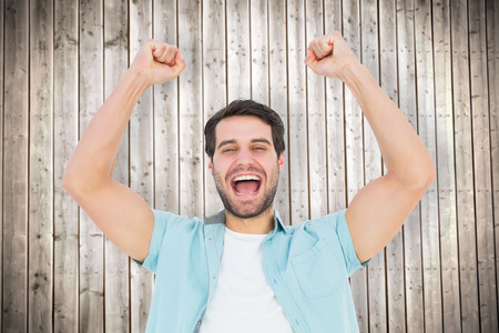Happy casual man cheering at camera against wooden planks background