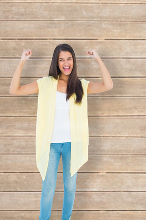 Happy casual woman cheering at camera against wooden planks