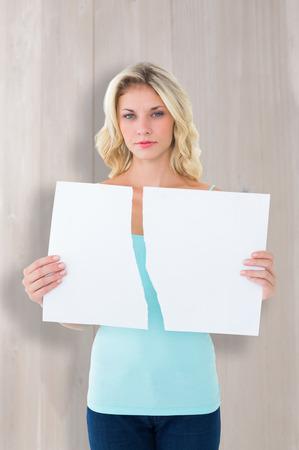 Sad blonde holding a broken card against bleached wooden planks background