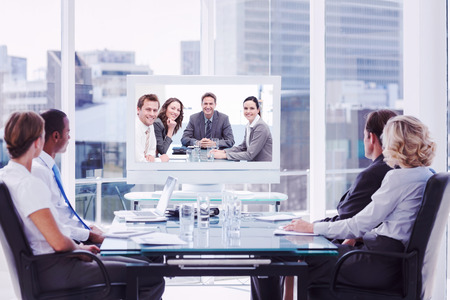 Photo pour Group of business people looking at a screen against portrait of a positive team sitting at a table - image libre de droit