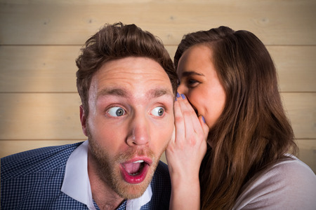 Woman whispering secret into friends ear against bleached wooden planks background