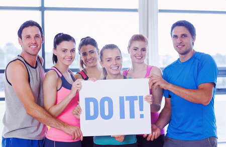 The word do it! against portrait of a group of fitness class holding blank paper