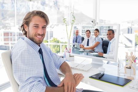 Foto de Business people brainstorming  against smiling designer sitting at his desk - Imagen libre de derechos