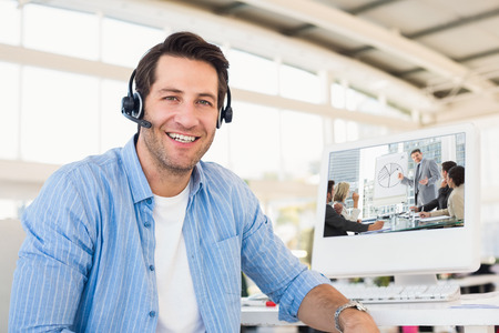 Business people in office at presentation against portrait of a smiling photo editor wearing a headset